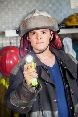 Confident Firefighter Holding Torch At Fire Station