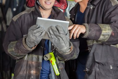 Male Firefighters Using Digital Tablet