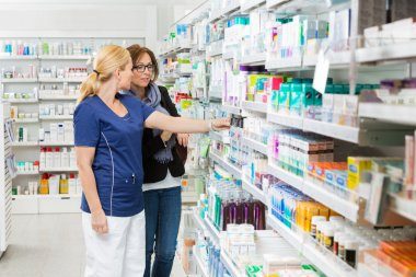 Pharmacist Removing Product For Customer From Shelf