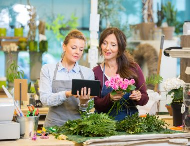 Florists Using Digital Tablet While Making Bouquet In Shop