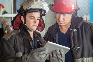 Firemen Using Digital Tablet At Fire Station