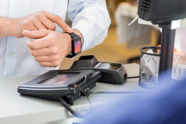 Customer Paying Through Smartwatch At Counter In Pharmacy
