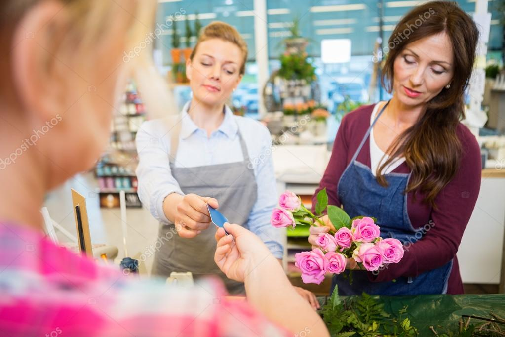 Florists Selling Rose Bouquet To Customer In Shop