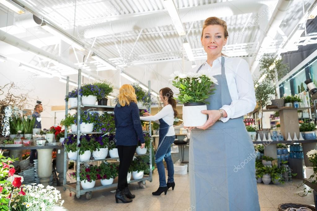 Happy Salesgirl Holding Flower Pot In Florist Shop