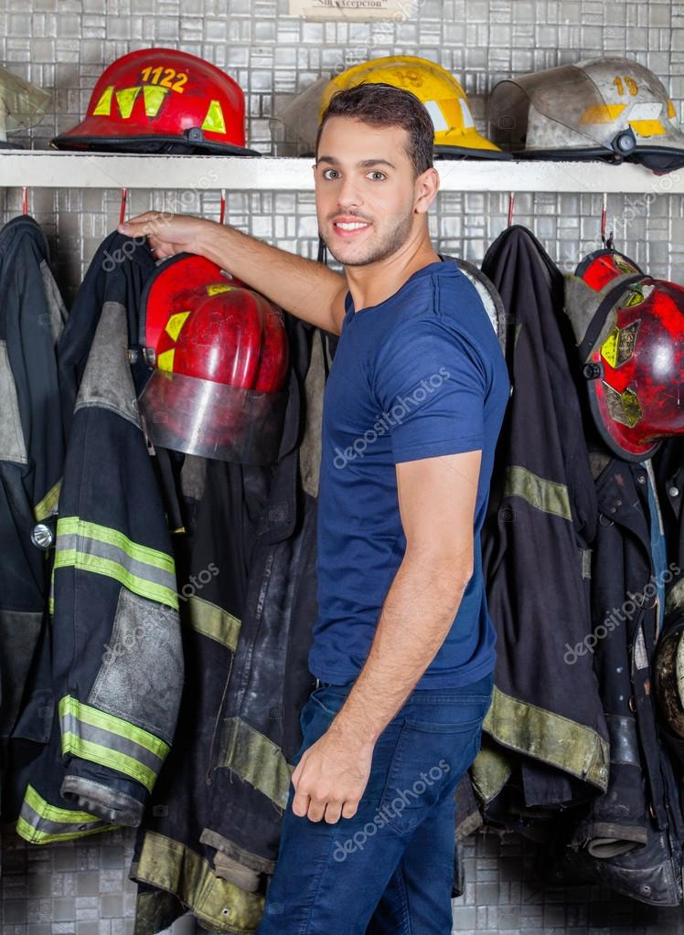 Fireman Removing Uniform Hanging At Fire Station