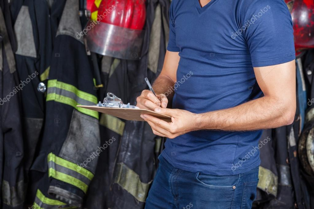 Firefighter Writing On Clipboard