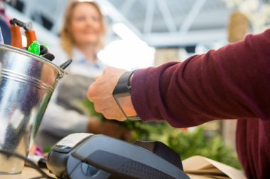 Customer Paying Through Smart Watch At Flower Shop