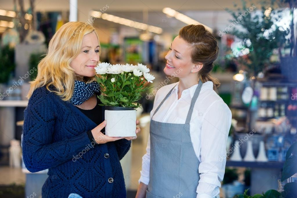 Florist Looking At Customer Smelling Flowers In Shop