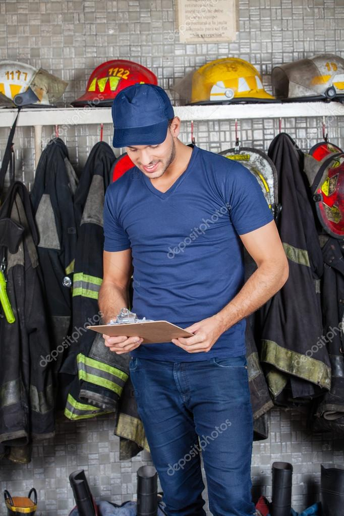 Fireman Reading Clipboard At Fire Station