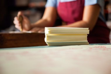 Papers On Table With Female Worker Working In Background