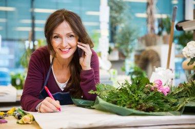 Happy Florist Taking Order In Flower Shop