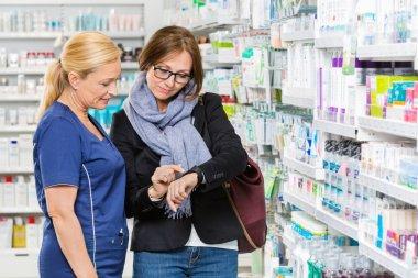 Customer Showing Medicine Information To Chemist On Smartwatch