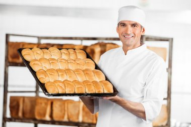 Mature Baker Showing Breads In Baking Tray