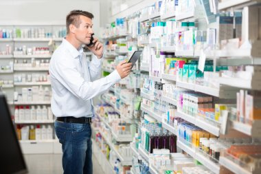 Male Customer Using Mobile Phone And Digital Tablet In Pharmacy