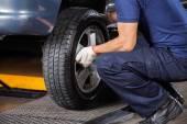 Fotografie Mechanik, oprava pneu auto v opravně