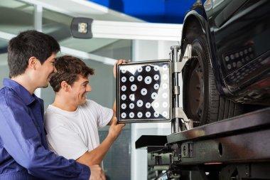 Mechanics Adjusting Wheel Aligner On Car