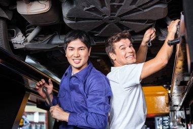Happy Mechanics Working Under Lifted Car