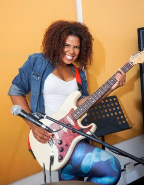 Excited Female Playing Guitar In Recording Studio