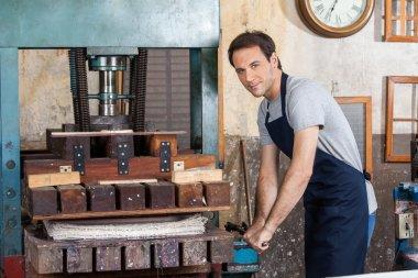 Man Using Paper Press Machine In Factory
