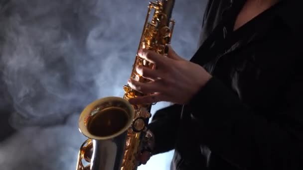 Füstölt háttérrel izolált szaxofonon játszó kezek közelsége