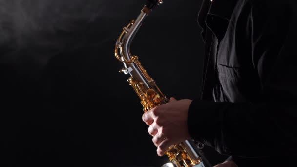 Szoros kéz játszik szaxofon elszigetelt fekete alapon