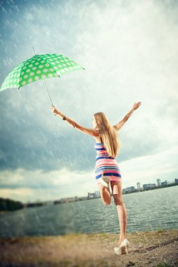 girl under an umbrella walks in the rain