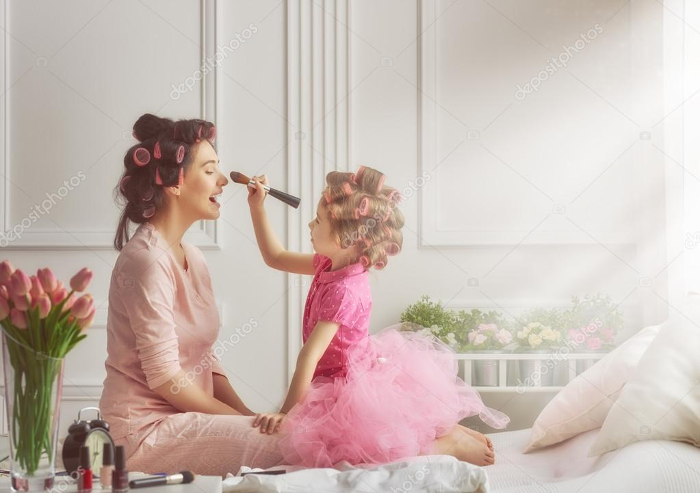 Happy loving family. Mother and daughter are doing hair and having fun. Mother and daughter doing your makeup sitting on the bed in the bedroom. stock vector