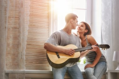 Happy couple in love. Stunning sensual portrait of young stylish fashion couple indoors. Young man playing guitar for his beloved girl. stock vector