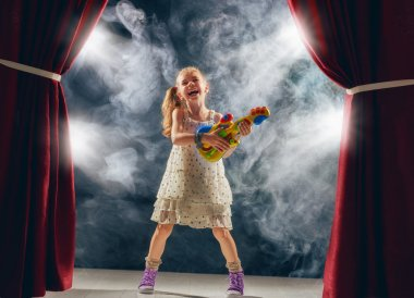 girl playing guitar on stage