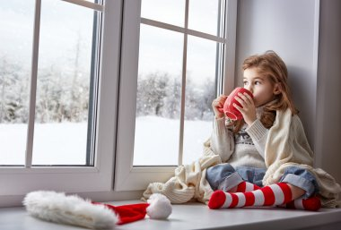 Little girl sitting by the window with a cup of hot drink and looking at the winter forest stock vector
