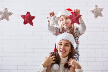 mother and daughter hang a garland