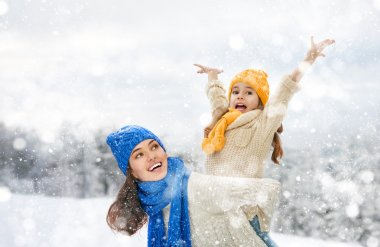 Mother and child girl on a winter walk