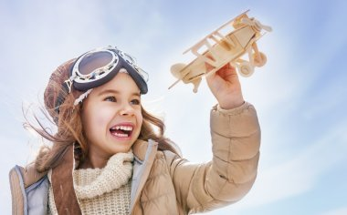 girl playing with toy airplane