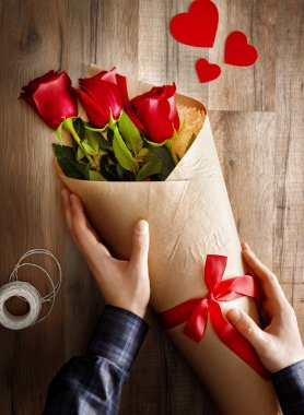 Male hands holding red roses on wooden background. the concept of love and Valentine's day. stock vector