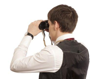 Businessman looks through a binoculars