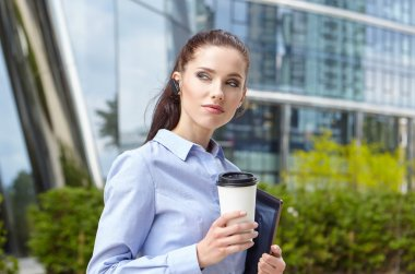 Businesswoman Walking On Street Holding Coffee