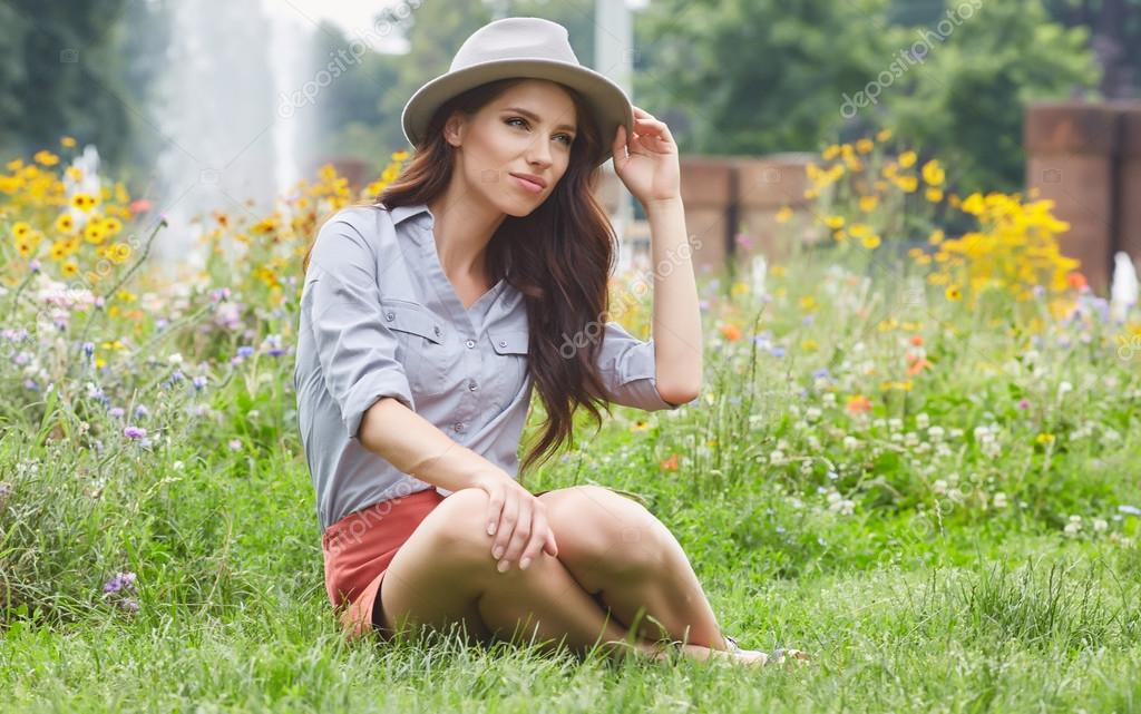 Spring woman sits on grass