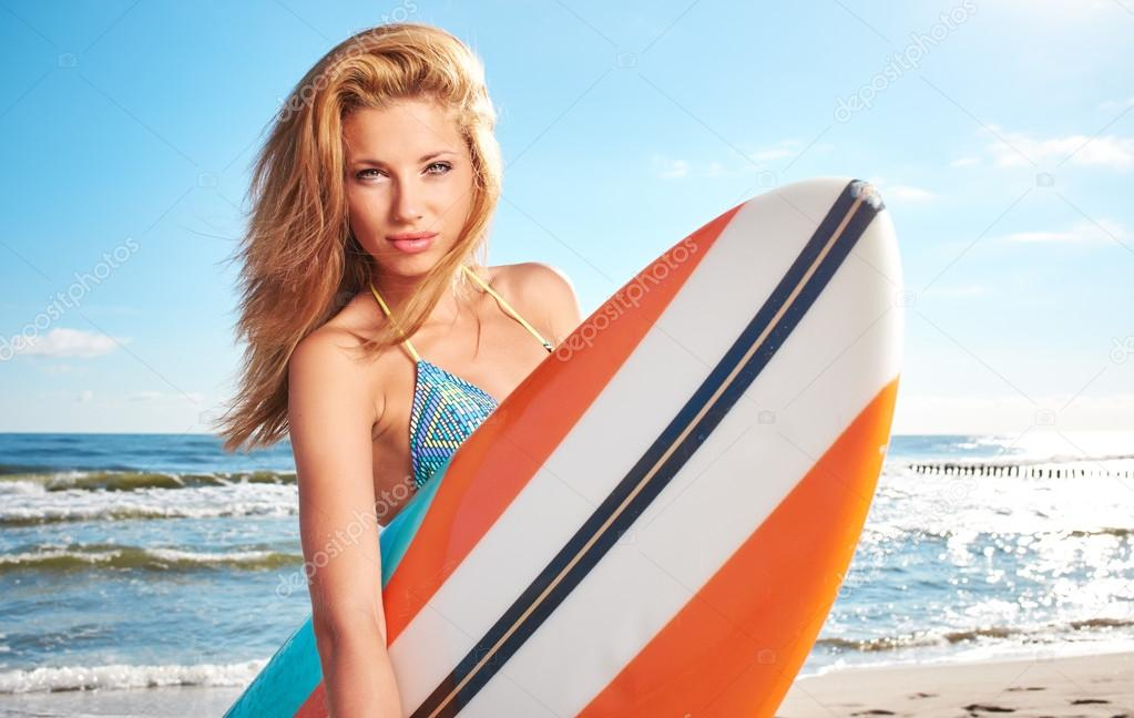 Surfer Girl Posing With Her Surfboard Stock Photo