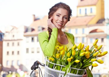girl sitting on bicycle with spring flowers
