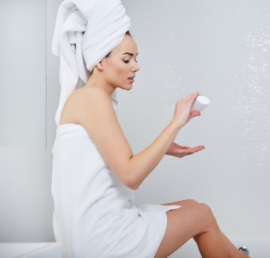Woman Wrapped with Bath Towels, Applying Cream on her Face