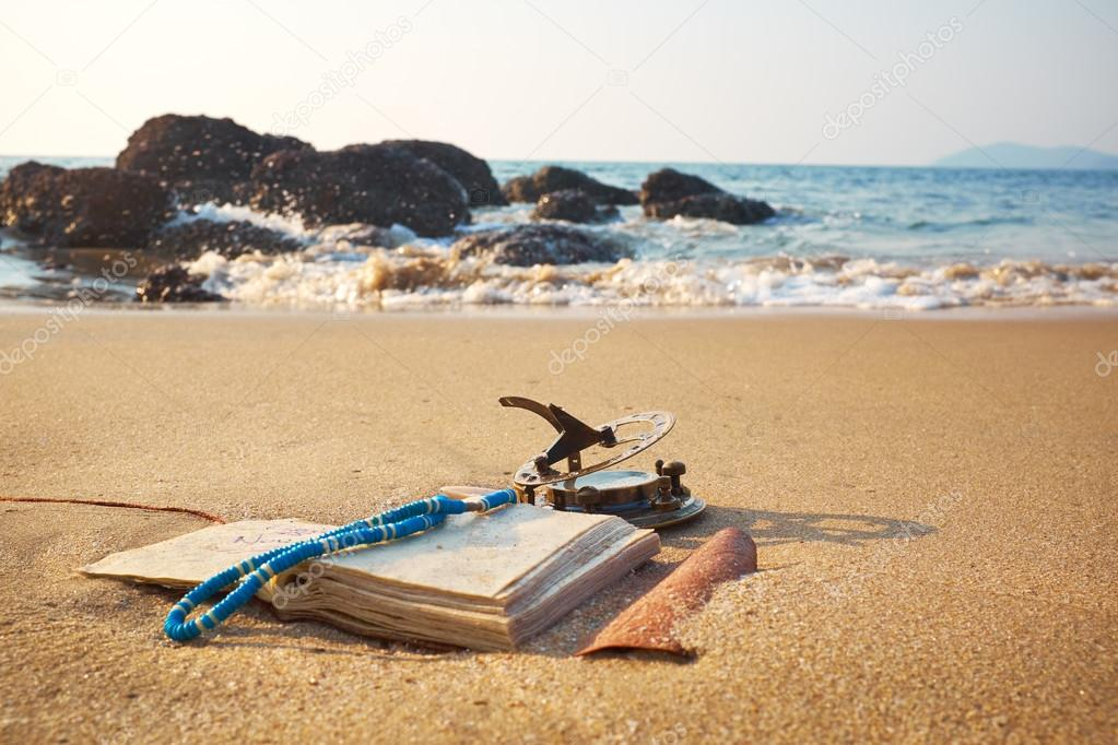 beach with vintage sundial and notebook