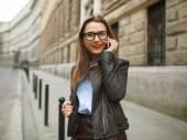 Podnikatelka, chůze po ulici, když mluví chytrý pho
