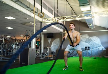 Man with battle rope in functional training fitness gym