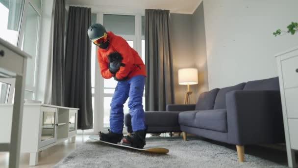 Lustiges Video. Ein als Snowboarder verkleideter Mann fährt auf einem Teppich in einem gemütlichen Raum auf einem Snowboard. Er hält eine schwarze Katze im Arm. Warten auf einen schneereichen Winter
