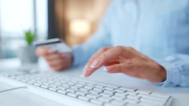 Weibliche Hände tippen die Kreditkartennummer auf die Computertastatur. Frau, die online einkauft. Online-Bezahldienst.