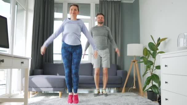 Caucasian couple is doing jumping jacks exercise at home in cozy bright room, slow motion.