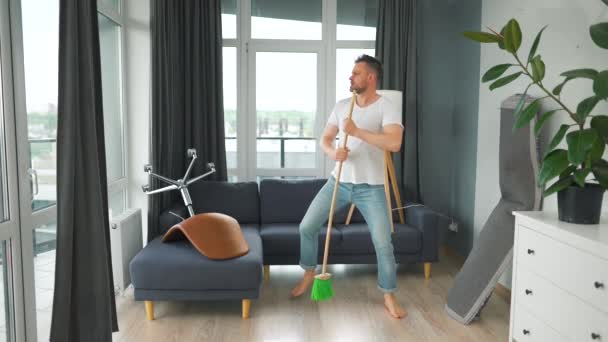 Man cleaning the house and having fun dancing and singing with a broom. Slow motion