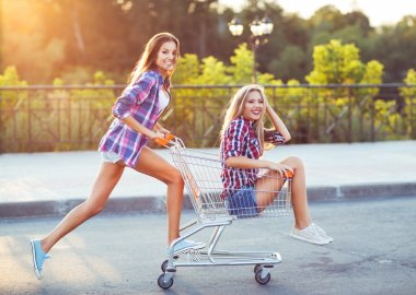 Two happy beautiful teen girls driving shopping cart outdoors