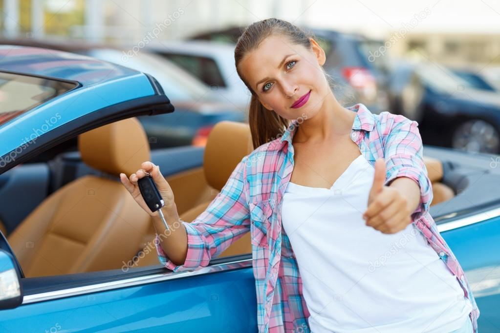 Young happy woman standing near a convertible with the keys in h
