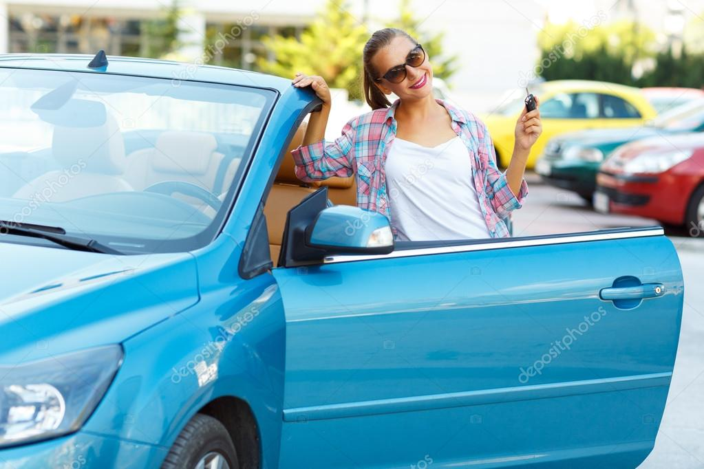 Woman in sunglasses standing near convertible with keys in hand